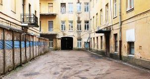 Le yard abandonné abandonné d'une maison de ville jaune Image stock
