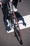 Le yclist de ¡ de Ð sur le vélo de route traverse la rue à la croix piétonnière Images libres de droits