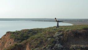 Le yoga d'Acro sur la montagne, fille sportive équilibre sur des jambes de son associé masculin au pré sur le fond de la mer clips vidéos
