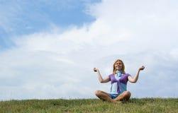 Le yoga de matin s'exerce au-dessus du ciel bleu avec des nuages. Image stock