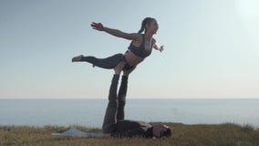 Le yoga de pratique d'acro de couples sportifs sur la montagne, acrobate féminin équilibre sur des jambes de son associé masculin clips vidéos
