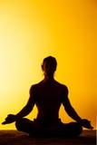 Le yoga de pratique d'homme dans la lumière de coucher du soleil Photographie stock libre de droits