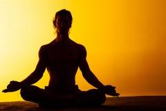 Le yoga de pratique d'homme dans la lumière de coucher du soleil Photo stock