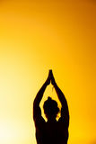 Le yoga de pratique d'homme dans la lumière de coucher du soleil Photos stock