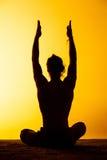 Le yoga de pratique d'homme dans la lumière de coucher du soleil Photo libre de droits