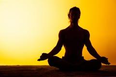 Le yoga de pratique d'homme dans la lumière de coucher du soleil Photos libres de droits