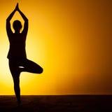 Le yoga de pratique de femme dans la lumière de coucher du soleil Photographie stock libre de droits