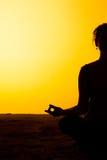 Le yoga de pratique de femme dans la lumière de coucher du soleil Images libres de droits