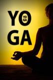Le yoga de pratique de femme dans la lumière de coucher du soleil Image libre de droits