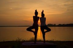 Le yoga de pratique de femme de la silhouette deux de YOGA pose sur des rivières de coucher du soleil Photo stock