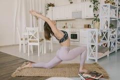 Le yoga de pratique de jeune femme caucasienne, Virabhadrasana a tourné la pose de guerrier dans la cuisine Faire de sourire de j photographie stock libre de droits