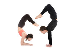 Le yogi couple dans la pose de scorpion de yoga Photo stock