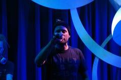Le yogi de MC ferme des yeux pendant qu'il chantent dans la MIC avec le DJ Drez derrière lui Image libre de droits