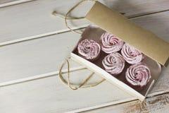 Le zéphyr rose dans la boîte de papier de métier sur le fond en bois blanc Photographie stock libre de droits