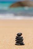 Le zen lapide jy sur la plage sablonneuse près de la mer. Images libres de droits