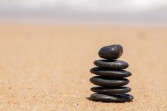 Le zen lapide jy sur la plage sablonneuse près de la mer. Photographie stock