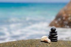 Le zen lapide jy sur la plage sablonneuse près de la mer. Photo stock