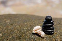 Le zen lapide jy sur la plage sablonneuse près de la mer. Photos stock