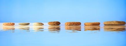 Le zen lapide la rangée sur le fond bleu images libres de droits