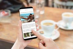 Lea el artículo de noticias con el teléfono elegante Sitio web porta de las noticias con la información del negocio imágenes de archivo libres de regalías
