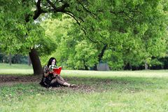 Lea un libro que se sienta bajo un ?rbol del flor fotografía de archivo
