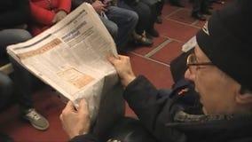Lea un periódico en el subterráneo metrajes