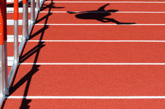 In the lead. Shadow of a person jumping over a hurdle on a red track Stock Photo