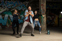 Lead dancer performing with crew. Portrait of a young handsome lead dancer and his crew performing in an abandoned building Royalty Free Stock Photos
