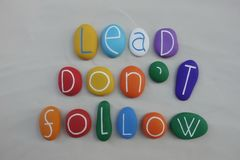 Lead, Don't Follow, motivational quote with colored stones over white sand stock photo