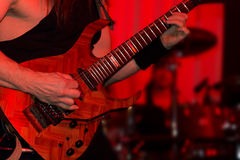 Lead guitarist playing electric guitar in a band. Lead guitarist playing electric guitar in a rock or jazz band during a live performance under red spotlights Stock Photography