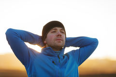 Lead a healthy lifestyle. A young man in sports clothes rests after jogging and breathes deeply Stock Image