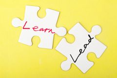 Lead or learn. Lead and learn words written on two pieces of jigsaw puzzle Royalty Free Stock Image