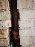 Lead pipe in a cracked brick wall Stock Photo