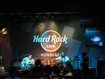 Lead singer of Guidance Band sings into mic while wearing sunglasses as he Jams on guitar on stage at Hard Rock Cafe royalty free stock image