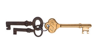 Lead the way. A golden key with engraved dollar sign and two rusted ones Royalty Free Stock Photos