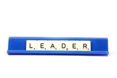 Leader. Scrabble pieces spelling the word LEADER on a blue board Royalty Free Stock Image
