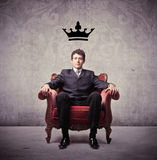 Leader. Young businessman sitting on an armchair with a crown over his head Stock Photos