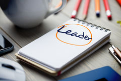 Leader against notepad on desk Royalty Free Stock Photography