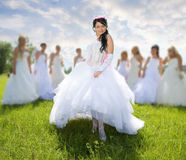 Leader bride with groups of bride. On green grass royalty free stock images