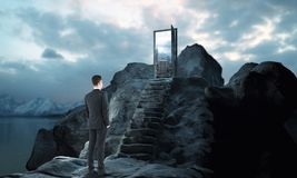 Leader concept. Thoughtful young businessman next to mountain steps leading to abstract open door with view on sky background. Leader concept. 3D Rendering Stock Photo