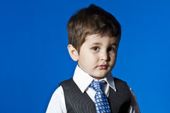 Leader, cute little boy portrait over blue chroma background. Tie, cute little boy portrait over blue chroma Royalty Free Stock Image