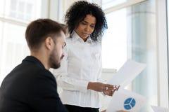 Leader della squadra e collega che esaminano le statistiche indicate sul documento immagine stock libera da diritti