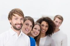 Leader della squadra sorridente di affari con il suo gruppo Immagine Stock