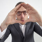 Leader expressing concept of perspective,focus or corporate frame. Expressive corporate man concept - fun middle age businessman staring at the camera for vision Royalty Free Stock Images