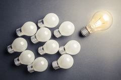 Leader and Follower. Glowing light bulb as leader with many small bulbs as follower Royalty Free Stock Photo