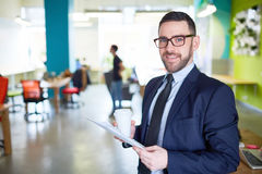 Leader in formalwear. Business leader with paper and drink looking at camera Stock Photography