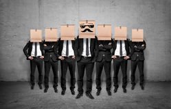Leader and his staff staying together with boxes on their heads. On concrete background. Teamwork. Business management. Leadership Royalty Free Stock Photography