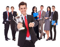 Leader holding a big trophy cup and pointing. Winning business team with leader holding a big trophy cup and pointing to you, on white background royalty free stock photos