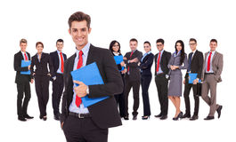 Leader holding a clipboard with business team behind royalty free stock photos