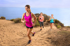 Leader jogger running uphill extreme workout fitness in shape weight loss exercise team row modern. Exercise team fitness group Yoga class at beach beautiful royalty free stock image
